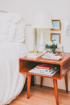White ruffled bedding and wooden midcentury nightstand