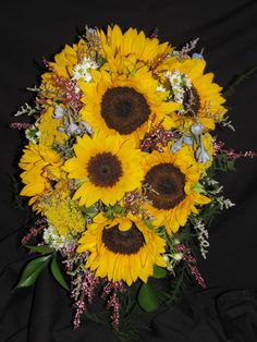 Cascade bouquet created with yellow sunflowers with dark centers, yellow yarrow, white Monte casino, pink calcinia heather, purple caspia, and light blue delphinium, with mixed greenery.