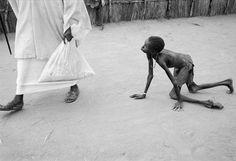 Un hombre sudanés bien nutrido roba el maíz de un niño hambriento durante la distribución de alimentos de Médicos Sin Fronteras centro de alimentación, Ajiep, Sudán, en 1998. El muchacho esquelético había esperado durante horas para recibir los suministros muy limitadas de ayuda disponibles. Por Stoddart