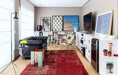 Na sala de TV projetada pelo arquiteto Maurício Arruda há dois tapetes, um sobre o outro. O maior e mais básico ficou por baixo e cobriu praticamente todo o piso. Por cima dele, o modelo vermelho dá um ar mais descontraído
