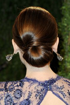 Lily Collins's chignon looks simple, but the sideswept top section requires a bit of extra work. You'll need two sections of hair, a base that makes the chignon, and a smaller, smooth section to swoop over the top and underneath
