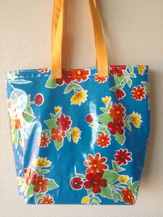 Mexican ethnic bag. Beautiful blue and flowers oilcloth pattern design with yellow handles.  Made with highly resistant waterproof materials.