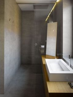 shower with sliding glass doors and  concrete walls