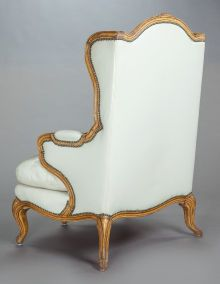 Furniture : French, A LOUIS XV-STYLE GILT WOOD BERGÈRE UPHOLSTERED IN WHITE LEATHER.First quarter 20th century. 47 x 35 x 32-1/2 inches (119.4 ...