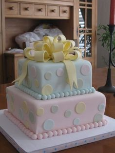 Baby shower cake for twins - a boy and a girl.  Covered with fondant, fondant bow, polka dots and balls.