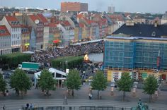 """Nyhavn (New Port) area in Copenhagen, Denmark. The fire is where they are burning a witch at stake to recognize the equinox. Princess """"Star"""" Ship."""
