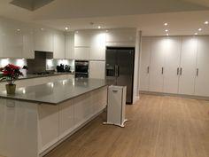 Finally. My very own kitchen that I love.   White high gloss handle less units. Light grey quartz worktops. Oak laminate floors.