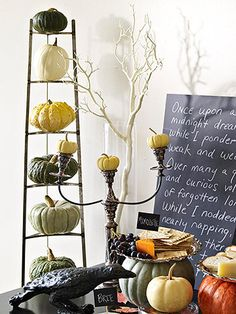 Love this display~ stand tree branches, {spray-painted white -or- black}, in tall glass vases filled with polished black rocks to create a textural element that casts spooky shadows. Stack different pumpkin varieties on surfaces throughout the space, such as mini pumpkins on candelabras and multicolor pumpkins on a triangular pot stand.