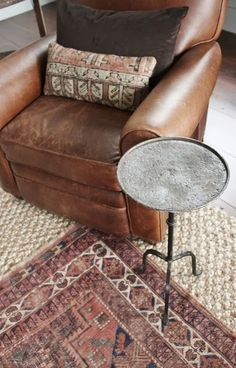 leather chair, tribal rug layered over natural rug