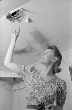 A DAY IN THE LIFE OF A WARTIME HOUSEWIFE: EVERYDAY LIFE IN LONDON, ENGLAND, 1941 ~ Mrs Day points to a hole in the ceiling where a fire bomb recently came through into her South Kensington home. Scorch marks can be seen on the ceiling next to the hole.