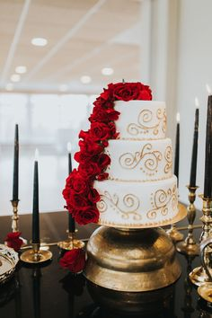 Gold wedding cake embellished with red roses