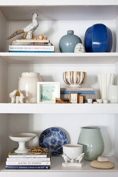 Think in Layers. Here is a shelf masterfully styled by Emily Henderson. Notice the balance achieved between the books alternating in placement from left to right with the ceramics poised on the opposite side. The middle shelf repeats the books plus ceramics combination, and also provides the opportunity to display smaller collectibles. Different heights and textures also add to the appeal.