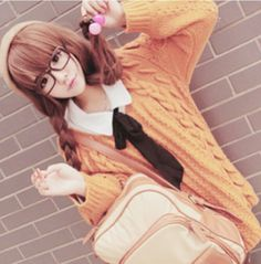 Cute, gyaru: Beige beret. Glasses. White shirt with black ribbon. Orange, cable knit cardigan. Creme backpack.