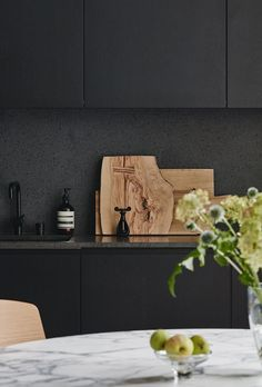 Painting it Black: Matte black cabinetry, stone counter and splash back together with the tapware contrast beautifully against the warm timber boards and greenery on display in the kitchen / Lahti Home | Joanna Laajisto | Est Living