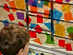 Make this easy faux kids stained glass window art project with colorful cellophane shapes. It's the perfect activity to camouflage a less-that-perfect view!