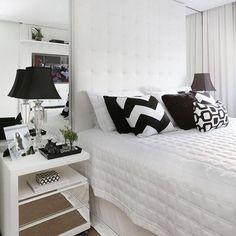 Cabeceira em couro branco com espelhos laterais até o teto.