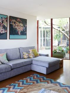 The living room, another view! Cinque Terra paintings by Laurie Mossuto. Cushions by Pony Rider and Cushionopoly, available from thewoodsfolk.com.au and the rug is one of Amber's felt ball creations. 'We do a lot of custom work and I customed this one just for us. I wanted colours that tied the artwork to the rest of the room and didn't clash with the cork flooring. Photo – Eve Wilson, production – Lucy Feagins / The Design Files.