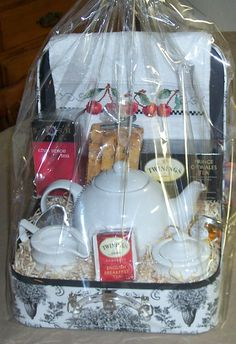 A tea themed gift basket with a hand -stitched tea towel and orange almond chocolate chip biscotti.