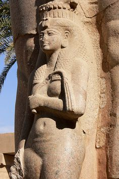 Karnak Temple Complex - Luxor/statue of a queen or princess standing against the leg of a Pharaoh.