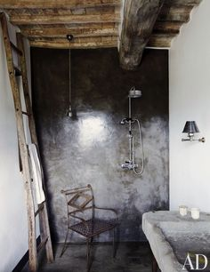 A guest bath in a home in Umbria, Italy, has a concrete-and-resin shower with Lefroy Brooks fittings; the stone sink is antique. Related: AD's Guide to Decorating with Color