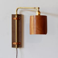 This leather wall sconce has a black walnut backplate, a brass arm and a hand sewn leather shade. The brass arm articulates to fulfill many different lighting needs. It can provide up lighting or down