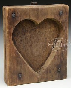 "Circa early 19th century, New England. Pine. Original surface. 2-piece mold, beveled edge heart square nailed to backboard, retaining its original leather hanging strap and brass ring. SIZE: 6"" x 5"" x 1"". CONDITION: Very good untouched condition, dark, natural patina. 9-96648"