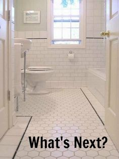 **White tiled bathroom described as classic. Maybe with white border pieces and cobalt
