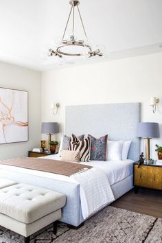 Modern bedroom with a chrome chandelier, a gray linen headboard, and an animal print throw pillow