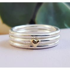 A slimline sterling silver stacking ring set where the central ring is accented…