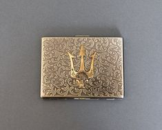 2e438fe92c49 This antique brass cigarette case has rounded corners with an ornate  embossed pattern on the front