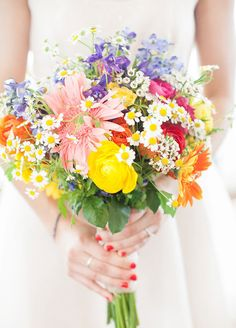 Don't play favorites! This bouquet, overflowing with everything from yellow ranunculus to white daisies, feels just as fun and carefree as the summer season itself.