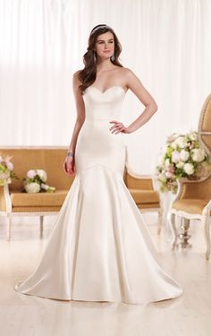 You'll love how this rich Dolce Satin bridal gown from the Essense of Australia wedding dress collection boasts modern lines on its sophisticated fit-and-flare silhouette. Choose from a corset closure or a zipper closure under satin-covered buttons that carry through to a chapel train. This dress is available in Ivory, Oyster, Pewter and White