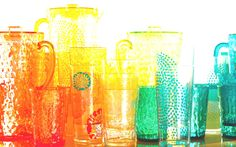 Close up of a variety of glasses and glassware on a table reflecting sunlight