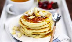Breakfast: pancakes with banana and coconut on white plate, cup of green tea, tea spoon and cranberries on white tray, close up