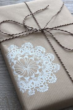 Gift wrap with pinstripe brown kraft paper, gold and black striped baker's twine and a white doily stamp