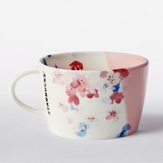 A ceramic mug with floral art and asymmetrical dipped pink glaze. Part of the Cherry Blossom Drinkware Collection.