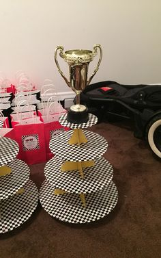 How to do a DIY race car theme cupcake stand. Buy checkered duct tape, yellow duct tape, and a plain cardboard cupcake stand from Michaels. Wrap the stand with the duct tape. Buy a novelty plastic trophy from party city and hot glue gun it to the top tier. Voila