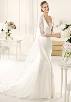 The Verso model from the Manuel Mota 2013 collection for Pronovias has a beautiful V-neck with soft draping. This mermaid wedding dress is made in delicate silky satin. The rounded back and lace coat with elbow-length sleeves gives the model an urban air. A beautiful skirt accentuates the unforgettable, flattering shape of this gown.