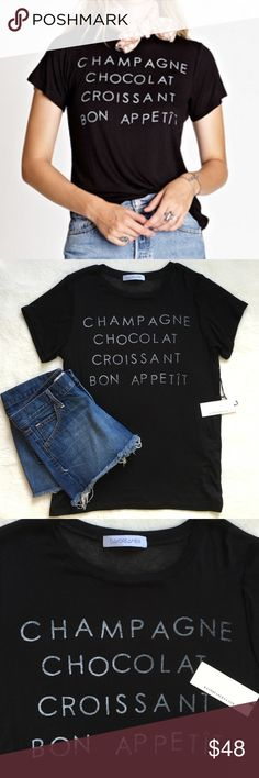 """{Daydreamer} Bon Appetit Tee NWT! This black tee has """"Champagne, Chocolat Croissant, Bon Appetît"""" at front in gray text, ribbing at neck, and a loose fit. Made from Daydreamer's signature fabric. Made in L.A. by Daydreamer. 96% rayon 4% spandex. Sold out online! Daydreamer Tops Tees - Short Sleeve"""