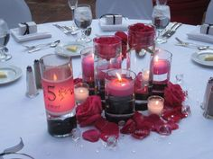 wedding idea-Different size cylinders with some hot pink floating candles, and some hot pink single roses. Use a velum paper for the table number so it doesn't take up space on table. Black ribbon around the bottom of cylinder with a rhinestone button. Rose petals and clear diamond shaped beads scattered around.