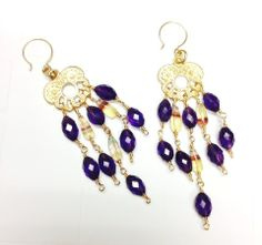 Deep purple, African Amethyst are beautifully faceted and combined with banded Fluorite to create this marvelous pair of earrings. Set on 24K Gold Plating on Brass filigree ear charms, these earrings are stunning! Light weight, bright and bold! Stones: African Amethyst, Banded Fluorite Materials: GP Ear Charms and 14/20 GF Earwires To see more designs, please visit: www.etsy.com/shop/ginnytaylordesigns