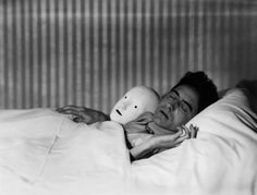 Jean Cocteau in bed with Mask, Paris, 1927. By Berenice Abbott
