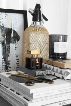 {mesh} gold bottle, black, gold, white, books, scissors, candle, tabletop styling, prop styling, home accessory styling -