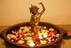 A brass urli, floating flowers and candles and the goddess Tara