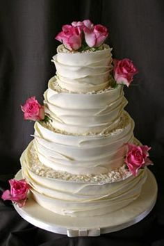 This gorgeous and creative four tier ivory wedding cake is decorated with pink roses and sheets of fondant and constructed around each of the tiers creating an amazing layer effect. Garnished with hot pink roses wedding cake topper. From www.flickr.com Scrumptious Cakes                       #wedding #cake #birthday