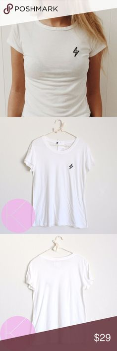 NWT Brandy Melville Lightning Tee Embroidery New with tags Brandy Melville lightning tee. Regular length NOT a crop top. Short sleeve. Embroidered lightning on the left. White.  One size.  Made in Italy Brandy Melville Tops Tees - Short Sleeve