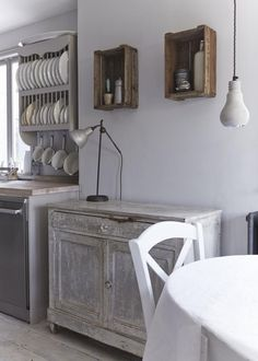 """Apple crates hang on the wall and are used as storage, while a dresser has been made from antique shutters.""""My motto is 'It's all in the mix',"""" she says. """"So I like to add the unexpected to break things up a bit. I particularly love the Concrete Pendant Lights above the kitchen table and I like to use harder, more masculine industrial pieces, to add an edge."""""""