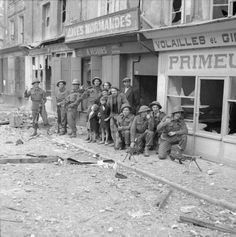 Tthe first British troops to enter Caen pose with local inhabitants outside wrecked shops. 9 july 1944