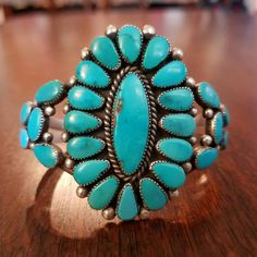 Vintage Zuni turquoise cluster cuff bracelet by world renown artist Alice Quam. Handmade from sterling silver and natural Castle Dome Turquoise. Measurements are approximately <2 inch wide across face 1 3/4 inch tall <2 1/4 inch length 5 1/4 inch inner circumference without gap <1 inch gap Bracelet size is inner circumference plus gap Bracelet can be minimally adjusted to size. Signed A.Q.