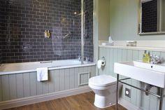 petite salle de bains avec baignoire douche, lambris mural gris perle et carrelage métro gris
